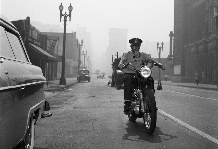 A Los Angeles motorcycle messenger making his routes in 1955 wearing a gas mask during a smog alert.